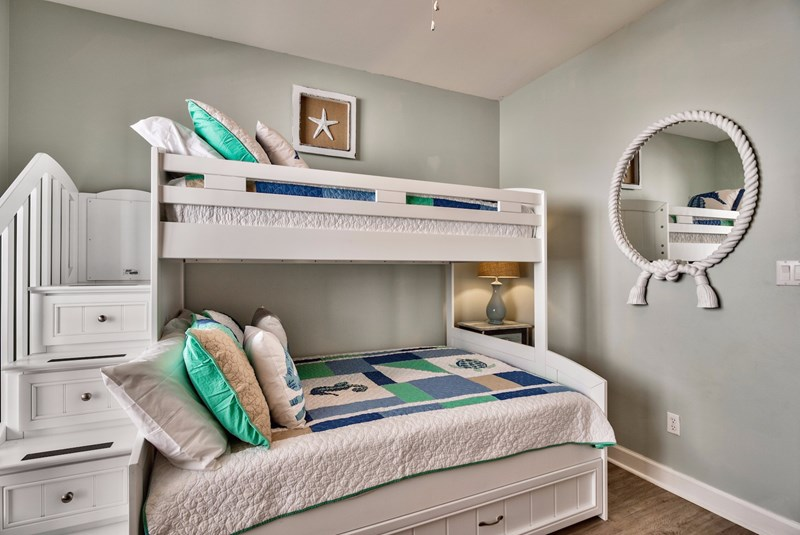 Storage drawers in stairs safely lead to top bunk bed.  Kids will love this room!