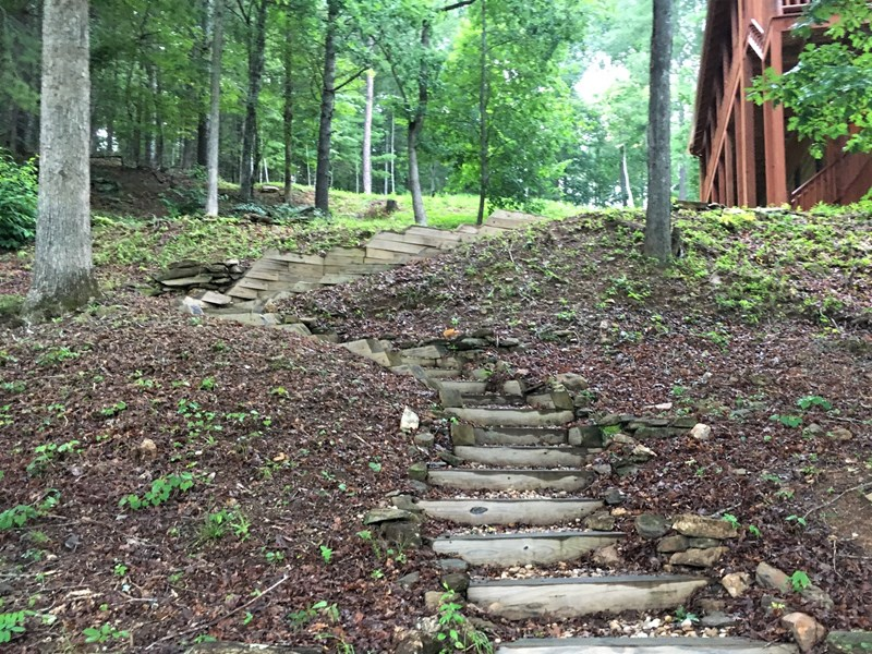 A gentle path leads down from the porch to the lake and fire pit area