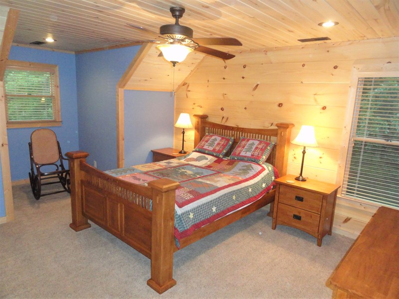 Upper level  - Bedroom #2 with queen bed, ensuite bathroom, and view to the lake