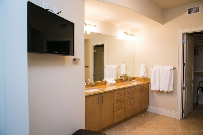 Master bath with double vanities and flat screen tv